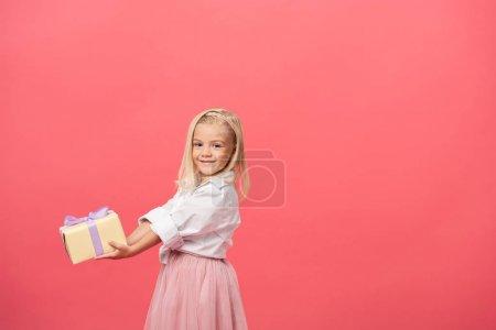 Photo for Cute and smiling kid holding gift isolated on pink - Royalty Free Image