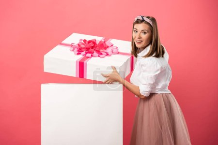 Photo for Attractive and smiling woman opening gift box isolated on pink - Royalty Free Image