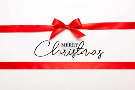 Photo for Top view of red ribbon and bow with merry christmas lettering on white - Royalty Free Image