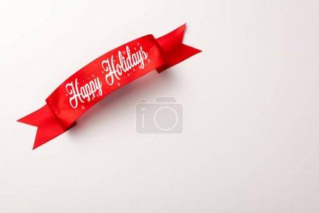 Photo pour Vue du haut du ruban rouge avec un lettrage joyeux des fêtes sur blanc - image libre de droit