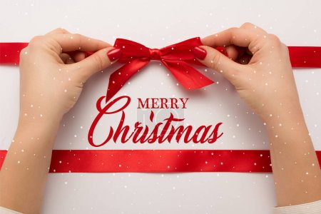 Photo for Cropped view of woman touching red bow near merry christmas lettering on white - Royalty Free Image