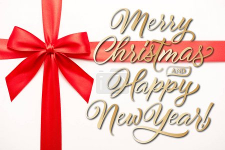 Photo for Top view of ribbon with red satin bow near merry christmas and happy new year letters on white - Royalty Free Image