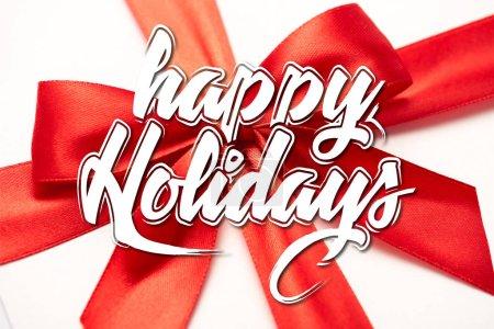 Photo pour Gros plan de ruban de satin avec arc rouge décoratif avec des lettres de fêtes heureuses sur blanc - image libre de droit