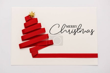 Photo pour Top view of red ribbon with golden star shape bow on paper envelope with merry christmas letters isolated on white - image libre de droit