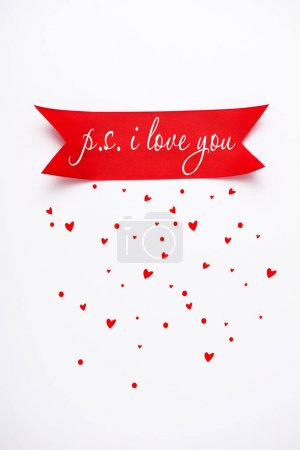 Photo pour Top view of red satin ribbon with p.s. i love you letters near falling hearts on white - image libre de droit