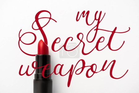 Photo pour Top view of black tube with red lipstick near my secret weapon letters on white - image libre de droit
