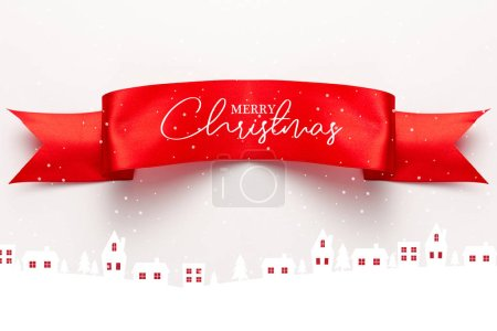 Photo for Top view of red satin ribbon with merry christmas lettering near houses and pines on white - Royalty Free Image
