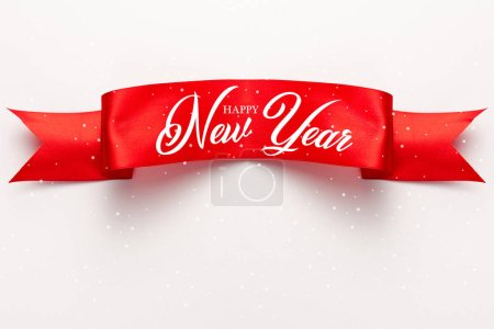 Photo for Top view of red satin ribbon with happy new year lettering on white - Royalty Free Image