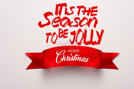 Photo for Top view of red ribbon with its the season to be jolly, merry christmas lettering on white - Royalty Free Image