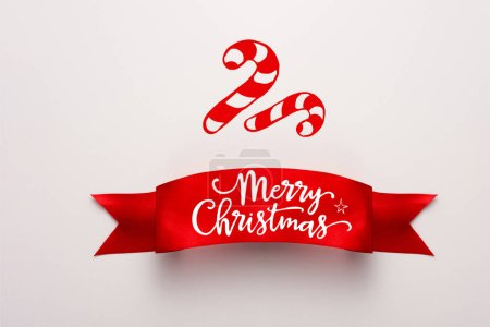Photo for Top view of red ribbon with merry christmas lettering near candy canes on white - Royalty Free Image