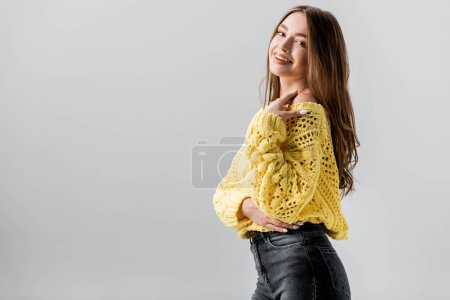 Photo for Cheerful girl looking at camera while holding hand near shoulder isolated on grey - Royalty Free Image
