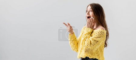 Photo pour Panoramic shot of shocked girl pointing with finger and touching face isolated on grey - image libre de droit