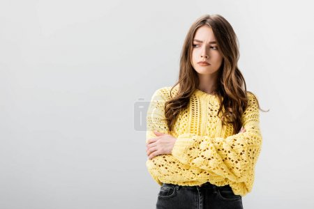 Photo for Offended girl in yellow sweater standing with crossed arms isolated on grey - Royalty Free Image