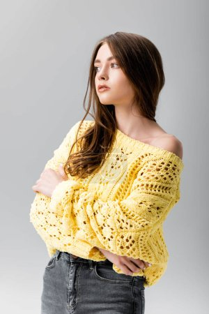 Photo pour Thoughtful girl in yellow sweater looking away while standing with crossed arms isolated on grey - image libre de droit
