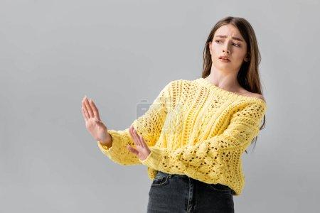 Foto de Chica disgustada en suéter amarillo mostrando gesto de stop mientras mira hacia otro lado aislado en gris - Imagen libre de derechos