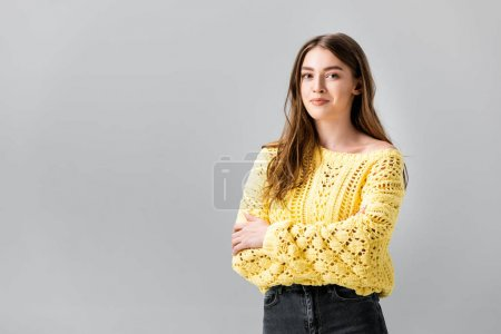 Photo for Positive young woman looking at camera while standing with crossed arms isolated on grey - Royalty Free Image