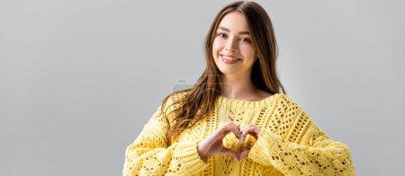 Photo pour Plan panoramique de fille souriante en pull jaune montrant signe cardiaque isolé sur gris - image libre de droit