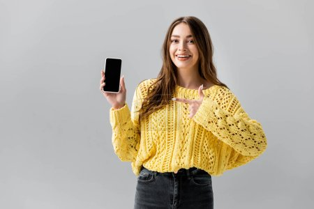 cheerful young woman pointing with finger at smartphone with black screen isolated on grey