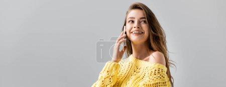 Photo pour Plan panoramique de fille souriante en pull jaune regardant loin tout en utilisant smartphone isolé sur gris - image libre de droit