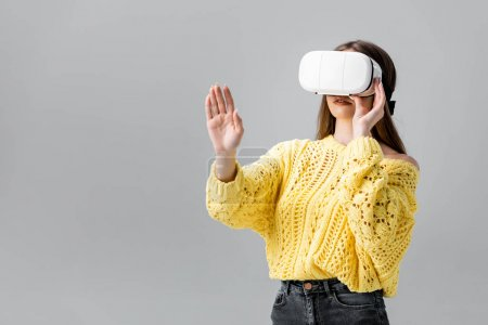Photo for Young woman in yellow sweater gesturing while using vr headset isolated on grey - Royalty Free Image