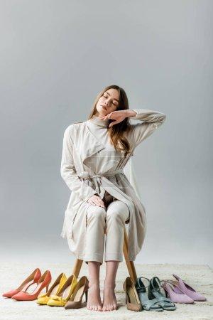 Photo pour Fille fatiguée et élégante assise sur une chaise près d'une collection de chaussures et touchant le visage avec la main sur fond gris - image libre de droit
