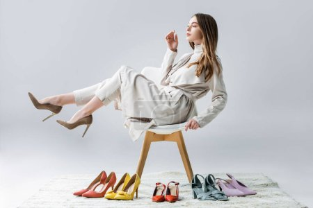 Photo for Thoughtful girl sitting on chair with raised legs near collection of shoes and looking away on grey background - Royalty Free Image
