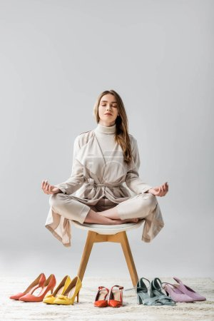 Photo pour Stylish girl sitting on chair in lotus pose near collection of shoes on grey background - image libre de droit