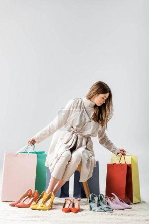 Photo pour Jeune femme branchée tenant des sacs à provisions alors qu'elle est assise près d'une collection de chaussures sur fond gris - image libre de droit