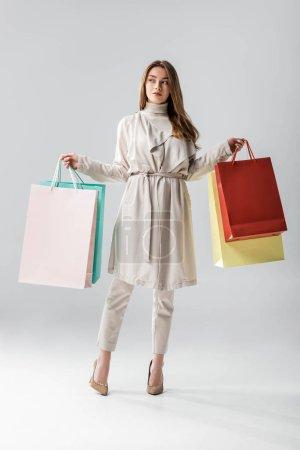 Photo pour Vue pleine longueur de fille élégante regardant loin tout en tenant des sacs à provisions sur fond gris - image libre de droit