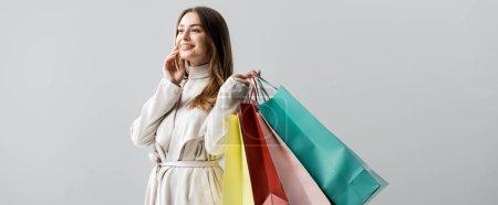 Photo pour Photo panoramique d'une fille de style regardant ailleurs en tenant les sacs isolés sur le gris - image libre de droit