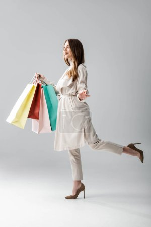 Photo for Full length view of happy girl in stylish cape holding shopping bags on grey background - Royalty Free Image