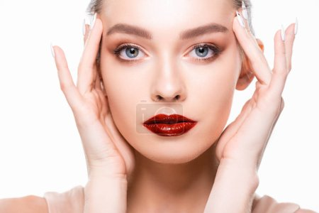 Photo pour Beautiful girl with red lips and makeup touching face while looking at camera isolated on white - image libre de droit