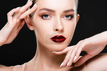 Photo pour Attractive young woman with red lips and makeup touching face while looking at camera isolated on black - image libre de droit