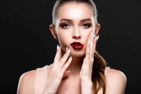 Photo pour Pretty young woman with red lips and makeup touching face while looking at camera isolated on black - image libre de droit