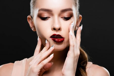 Photo pour Attractive young woman with red lips and makeup touching face isolated on black - image libre de droit