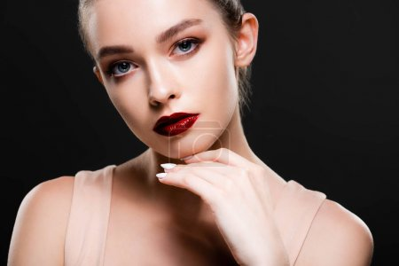 Photo pour Attractive young woman with bright red lips looking at camera isolated on black - image libre de droit