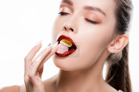 Photo pour Beautiful young woman with red lips and makeup eating candies isolated on white - image libre de droit