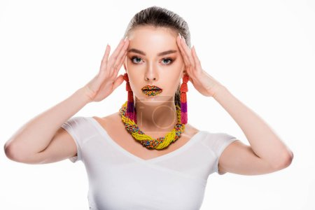 Photo for Beautiful girl in beaded accessories, with beads on lips, touching head and looking at camera isolated on white - Royalty Free Image