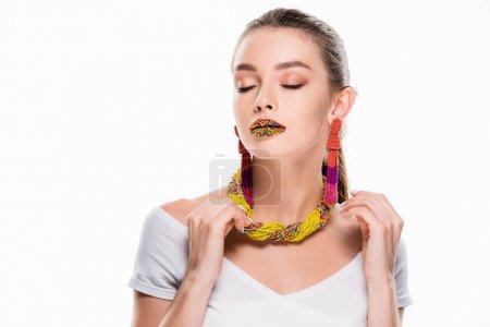 Photo pour Belle fille en accessoires perlés, avec des perles sur les lèvres, touchant collier isolé sur blanc - image libre de droit