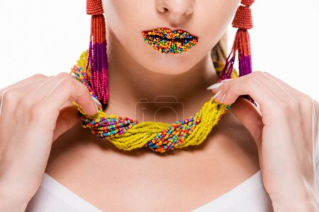 cropped view of girl with beads on lips touching beaded necklace isolated on white