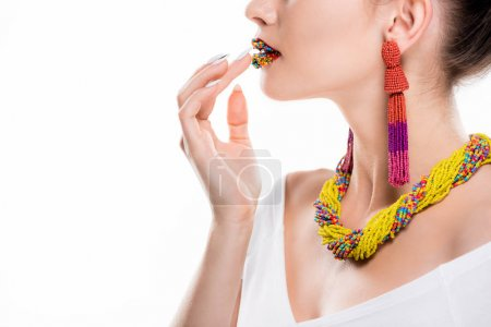 partial view of girl in beaded necklace and earrings touching beads on lips isolated on white