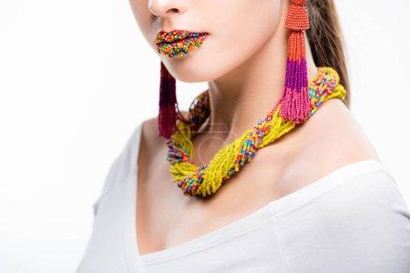 Photo pour Vue recadrée de la fille en collier perlé et boucles d'oreilles, avec des perles sur les lèvres isolées sur blanc - image libre de droit