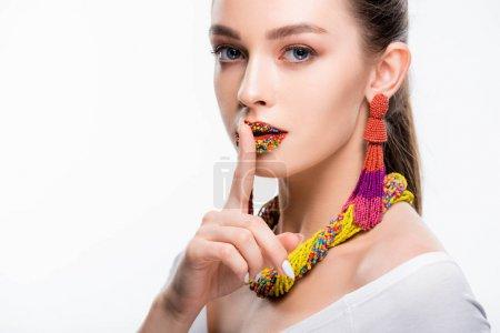 Photo pour Jolie fille en accessoires perlés, avec des perles sur les lèvres, montrant des signes de brousse et regardant la caméra isolée sur blanc - image libre de droit