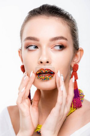 Photo pour Beautiful girl in beaded necklace and earrings touching beads on lips isolated on white - image libre de droit