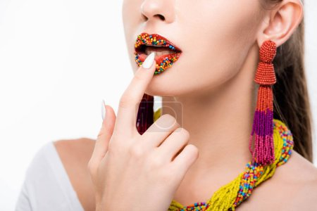 Photo pour Partial view of girl in beaded necklace and earrings touching beads on lips isolated on white - image libre de droit