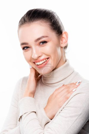 Photo pour Cheerful girl with natural makeup touching face and looking at camera isolated on white - image libre de droit