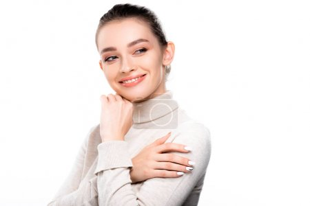 Photo pour Smiling girl with natural makeup touching face and looking away isolated on white - image libre de droit