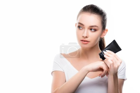 Photo pour Attractive girl looking away while applying hand cream isolated on white - image libre de droit