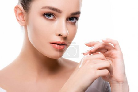 Photo pour Beautiful young woman applying hand cream and looking at camera isolated on white - image libre de droit