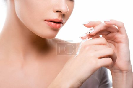 Photo pour Cropped view of young woman applying hand cream isolated on white - image libre de droit